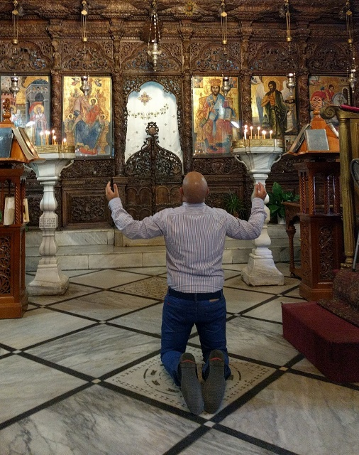 מתפלל כורע ברך בתוך כנסיית הבשורה האורתודוקסית בנצרת