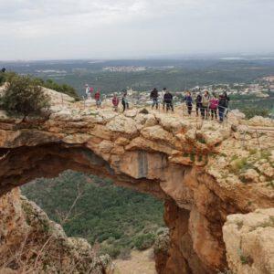 מטילים עומדים על הקשת במערת קשת כשנוף הגליל פרוס מאחוריהם